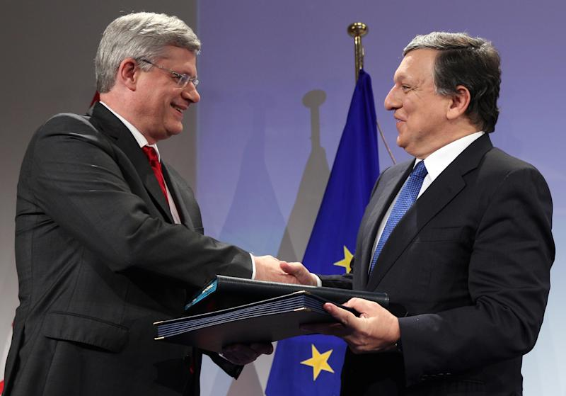 European Commission President Jose Manuel Barroso, right, shakes hands with Canada's Prime Minister Stephen Harper to conclude a signing ceremony at the European Commission headquarters in Brussels, Friday, Oct. 18, 2013. Canada and the European Union finalized a landmark free trade agreement to boost growth and employment in both economies. (AP Photo/Yves Logghe)