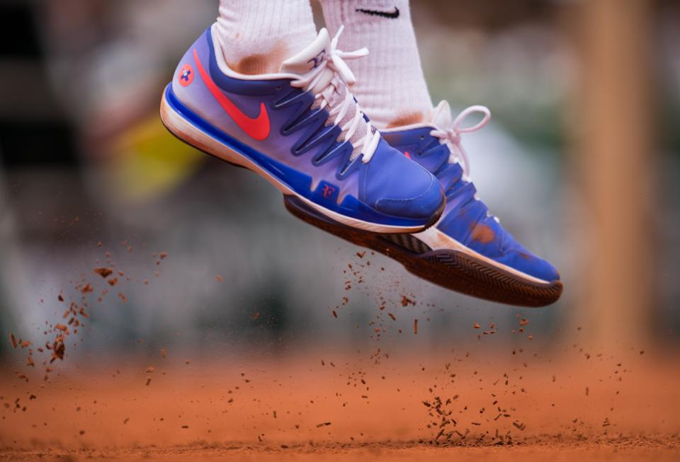 Roger Federer Nike shoes kick off the clay as he serves the ball during his 1st round men's singles match against Alejandro Falla on day one of the French Open at Roland Garros on May 24, 2015 in Paris, France