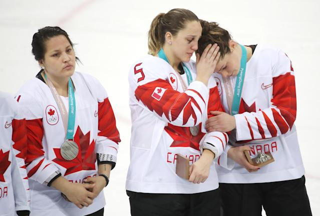 <p>Canada defenseman Lauriane Rougeau (5) consoles Canada forward Rebecca Johnston (6) after receiving their silver medals, Brigette Lacquette (4) is on the left as Canada loses in a shootout to the United States in the Olympic women's hockey gold medal game at the Gangneung Hockey Centre in Gangneung in Pyeongchang in South Korea. February 22, 2018. (Steve Russell/Toronto Star via Getty Images) </p>