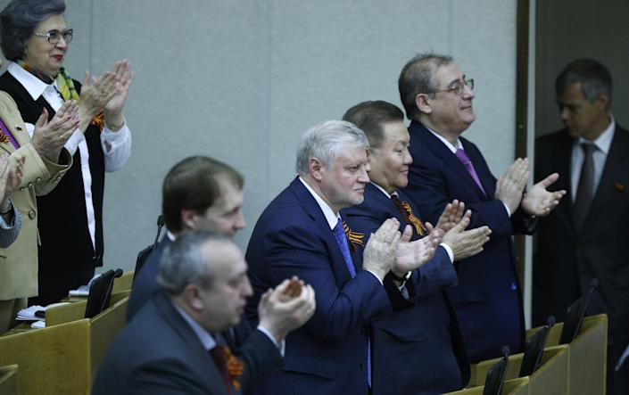 Members of the State Duma, lower parliament chamber, applaud for their voting during a plenary session in Moscow, Russia, Thursday, March 20, 2014. The Kremlin-controlled State Duma voted Thursday to allow Crimea to join Russia following a quick discussion in which members of the Kremlin-controlled chamber assailed the Ukrainian authorities. The merger needs to be rubber stamped by the upper house and signed by President Vladimir Putin, mere formalities expected to be completed by the end of the week. (AP Photo/Alexander Zemlianichenko)
