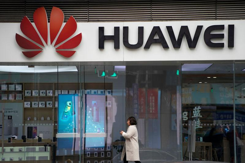 A woman walks by a Huawei logo at a shopping mall in Shanghai, China December 6, 2018. REUTERS/Aly Song