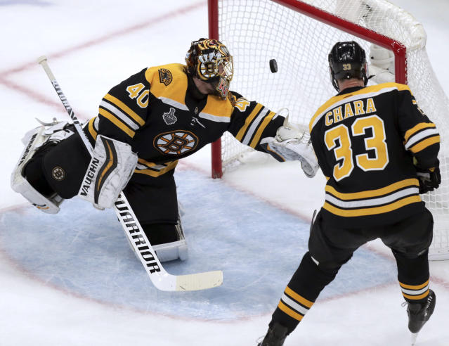 The puck bounces off the post behind Boston Bruins goaltender Tuukka Rask, left, of Finland, and Zdeno Chara, right, of Slovakia, during the second period in Game 7 of the NHL hockey Stanley Cup Final against the St. Louis Blues, Wednesday, June 12, 2019, in Boston. (AP Photo/Charles Krupa)