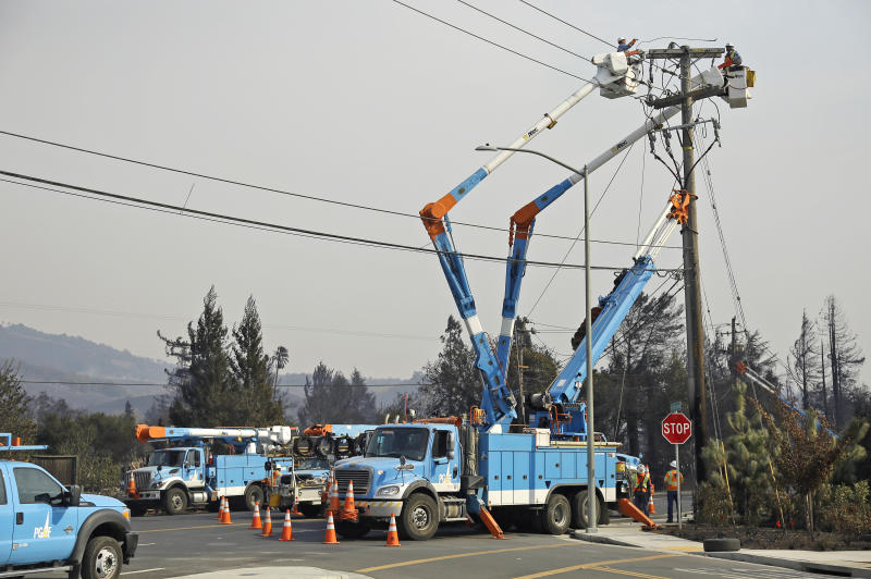"""FILE - In this Oct. 11, 2017 file photo, a Pacific Gas & Electric crew works at restoring power following a wildfire along the Old Redwood Highway in Santa Rosa, Calif. An Associated Press review shows widespread problems with the four """"public safety power shutoffs"""" the utility started rolling out in 2018, a year before massive blackouts paralyzed much of California in recent months. Interviews and documents obtained under public records requests reveal persistent failures and broken promises that in some cases compromised public safety. (AP Photo/Eric Risberg, File)"""