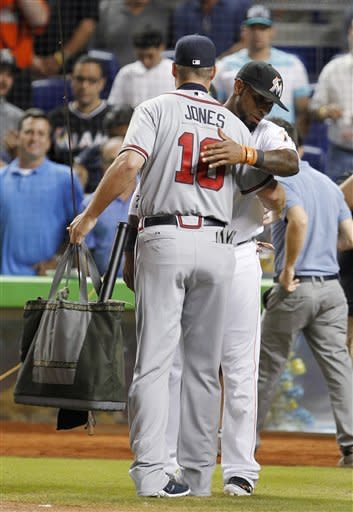 Atlanta Braves third baseman Chipper Jones (10) hugs Miami Marlins shortstop Jose Reyes after Jones received a fly-fishing rod and other gifts during a presentation before a baseball game between the Miami Marlins and the Atlanta Braves, Wednesday, Sept. 19, 2012, in Miami. Jones is retiring after the season. (AP Photo/Wilfredo Lee)