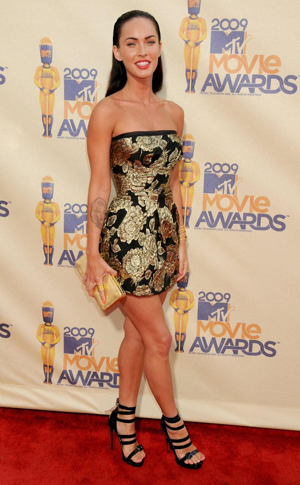 <p>Megan wore a gold and black floral mini dress with slicked back hair to the 2009 MTV Movie Awards. </p>