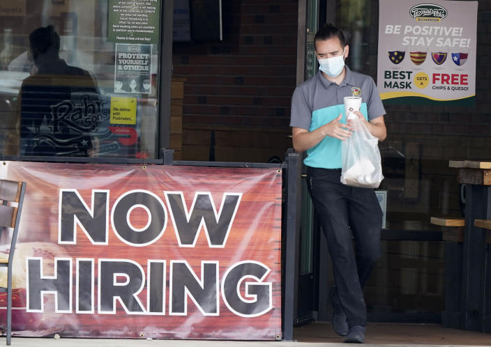 FILE - In this Sept. 2, 2020 file photo, a customer wears a face mask as they carry their order past a now hiring sign at an eatery in Richardson, Texas. On Thursday, Nov. 5, the number of Americans seeking unemployment benefits fell slightly last week to 751,000, a still-historically high level that shows that many employers keep cutting jobs in the face of the accelerating pandemic. (AP Photo/LM Otero, File)