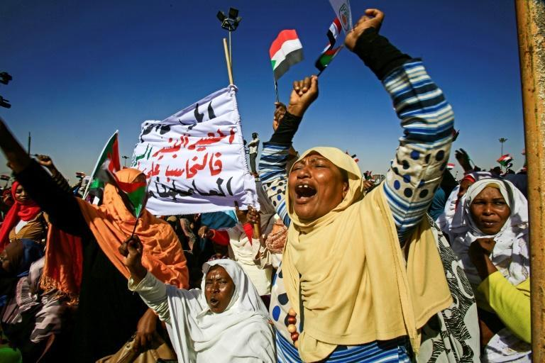 Supporters of Sudan's President Omar al-Bashir shout slogans as they gather during a rally for him in the Green Square in the capital Khartoum on January 9, 2019