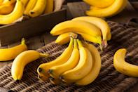 """<p>When you leave a bunch of bananas on the counter, they could remain green for days only to quickly over-ripen before you had a chance to use them. There are great ways to use overripe bananas — like <a href=""""https://www.thedailymeal.com/how-to-bake-bread-at-home?referrer=yahoo&category=beauty_food&include_utm=1&utm_medium=referral&utm_source=yahoo&utm_campaign=feed"""" rel=""""nofollow noopener"""" target=""""_blank"""" data-ylk=""""slk:homemade bana bread"""" class=""""link rapid-noclick-resp"""">homemade bana bread</a> — but if you use a storage trick or two, you can keep your bananas at optimal ripeness for longer. You should never store your bananas in the fridge if you want them to ripen; refrigerating bananas stalls the ripening of the inside of the fruit while accelerating the time it takes for the peel to brown and dry out. However, if a banana has reached optimal ripeness, you can stick it in the fridge unpeeled for a day or two to preserve the state of the inside fruit. Additionally, there's a trick for keeping bananas on the counter. Simply wrap the crown of a bunch of bananas in plastic wrap. This slows the release of ethylene gas, slowing down the ripening process.</p>"""