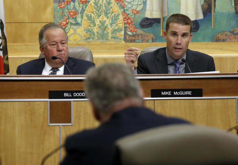 State Sen. Mike McGuire, D-Healdsburg, right, questions Pacific Gas & Electric CEO Bill Johnson, center, about the utilities' decision to turnoff power for millions of people to prevent wildfires during an oversight hearing of the Energy, Utilities and Communications committee at the Capitol in Sacramento, Calif., Monday, Nov. 18, 2019. Both McGuire and Sen. Bill Dodd, D-Napa, left, have had their districts affected by wildfires in recent years.(AP Photo/Rich Pedroncelli)