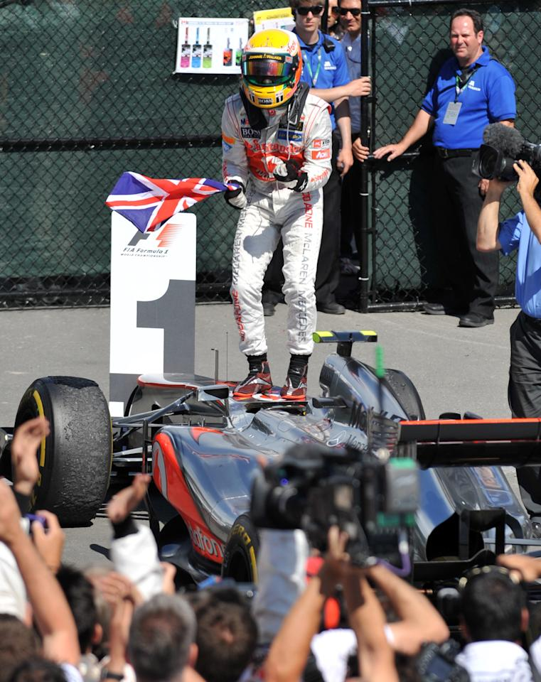 McLaren Mercedes driver Lewis Hamilton of Britain stands on his car as he celebrates his win in the Canadian Formula One Grand Prix on June 10, 2012 at the Circuit Gilles Villeneuve in Montreal.     AFP PHOTO/Stan HONDASTAN HONDA/AFP/GettyImages