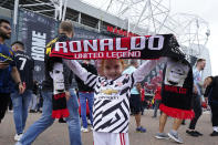 Edie Maisland, 5 years old, holds up a scarf with the name of Manchester United's Cristiano Ronaldo outside the stadium before the English Premier League soccer match between Manchester United and Newcastle United at Old Trafford stadium in Manchester, England, Saturday, Sept. 11, 2021. (AP Photo/Jon Super)