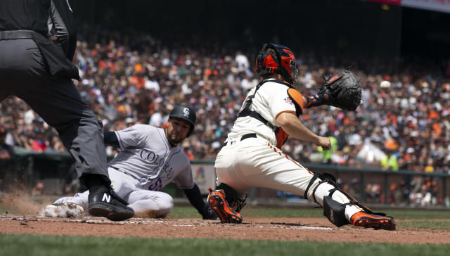 San Francisco Giants catcher Nick Hundley, right, prepares to put the tag on Colorado Rockies Noel Cuevas (56) who was trying to score on a double by Pat Valaika during the fourth inning of a baseball game, Sunday, May 20, 2018, in San Francisco. (AP Photo/D. Ross Cameron)