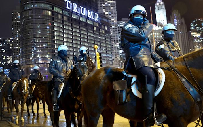 Police keep watch as a small group of demonstrators protest near Trump Tower in Chicago, Illinois - Scott Olson/Getty