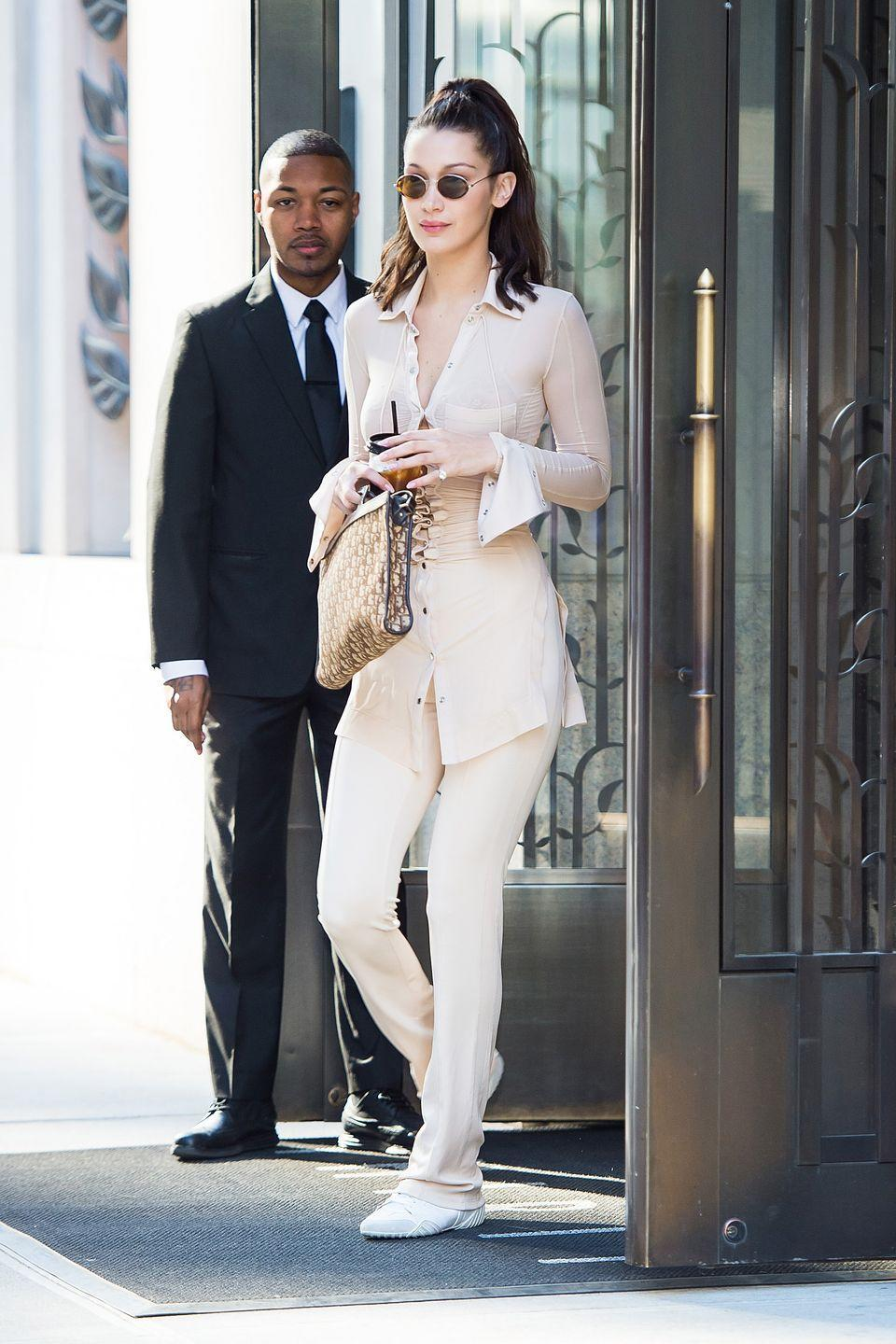 <p>In a beige button-down blouse and matching pants by Paco Rabbane, white sneakers, round sunglasses, and a Dior bag while out in New York.</p>