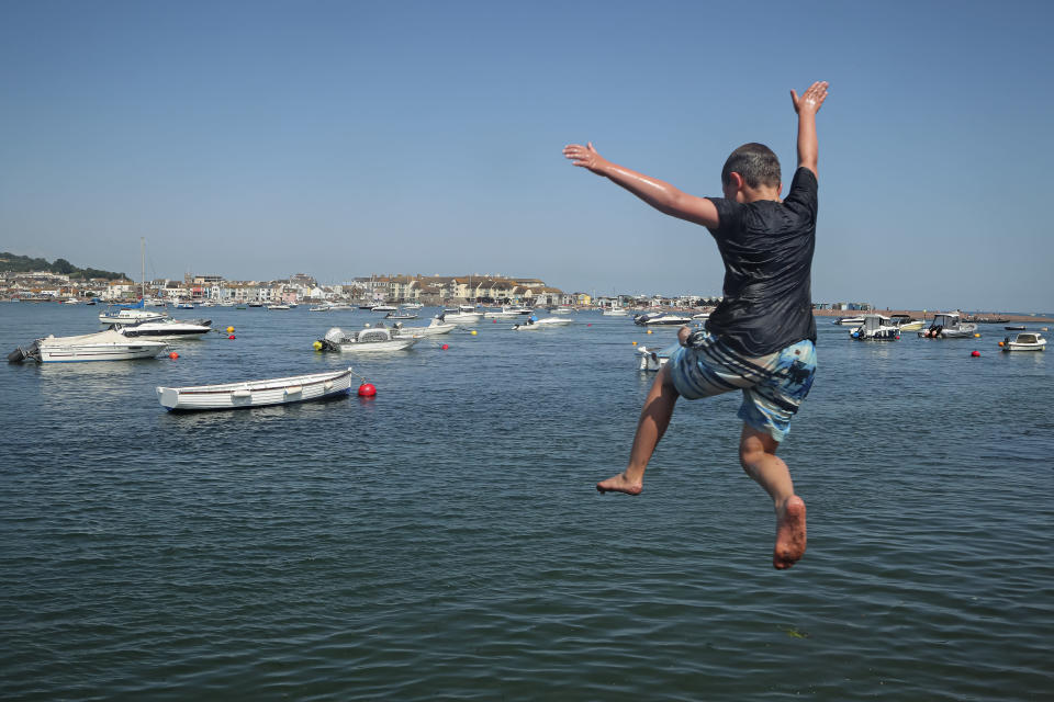 A boy jumps off a jetty into the Teign estuary in Shaldon, Devon, England, Wednesday July 21, 2021. Visiting the fishing village of Shaldon a small cluster of mainly Georgian houses and shops at the mouth of the River Teign, is like stepping back into a bygone era. It features simple pleasures that hark back to analog, unplugged summer days: a book and a picnic blanket, a bucket and spade, fish and chips. (AP Photo/Tony Hicks)
