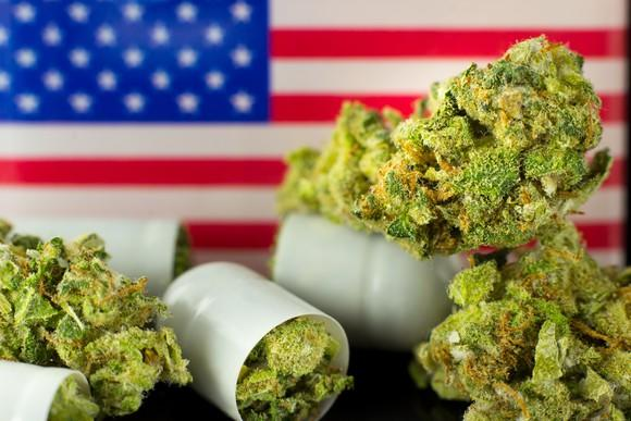 Marijuana buds spill out of bottles in front of a U.S. flag.