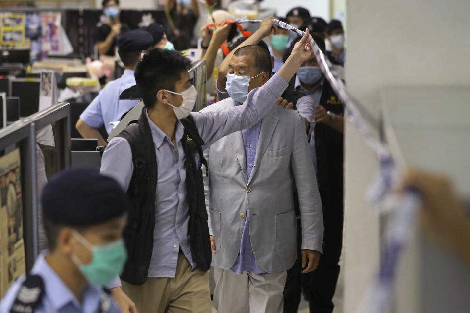 Hong Kong media tycoon Jimmy Lai, center, is escorted by police inside the Apple Daily newspaper headquarters in Hong Kong Monday, Aug. 10, 2020. Police arrested Lai and raided the newspaper's headquarters Monday in the highest-profile use yet of the new national security law Beijing imposed on the city in June. (Apple Daily via AP)