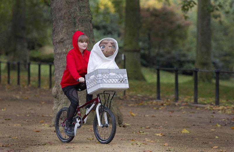 """This Oct. 19, 2012 photo made available on Oct. 22, shows a wax figure of ET from the 1982 Steven Spielberg film, """"E.T. the Extra-Terrestrial,"""" being carried in the basket of a bmx bicycle by Madame Tussaud's employee Amy, in central London, marking the Blu-ray edition release of the film. Tussauds will launch an ET wax figure in London, Berlin, Amsterdam, Sydney and Hollywood on Oct. 22. (Photo by Joel Ryan/Invision/AP)"""