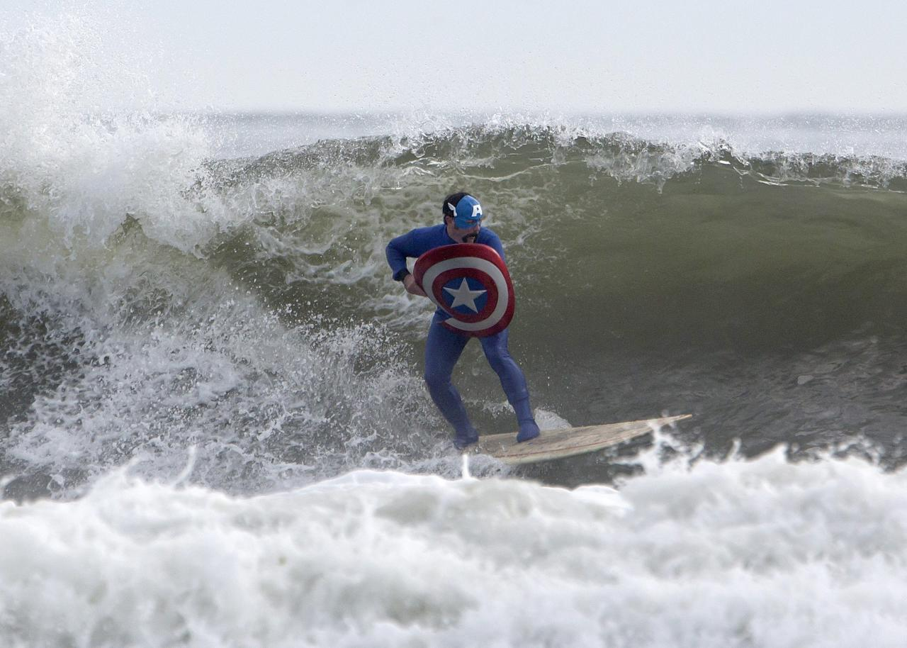 A participant dressed as Captain America surfs during the third annual Rockaway Halloween surf competition at Rockaway Beach in the Queens borough of New York November 2, 2013. REUTERS/Eric Thayer (UNITED STATES - Tags: SOCIETY)