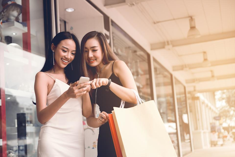 Two women at shopping mall center. (PHOTO: Getty Images)