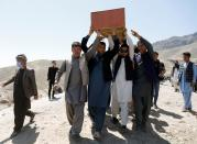 Afghan men carry the coffin of one of the victims of yesterday's explosion in Kabul