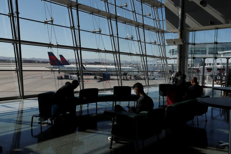 Travelers sit in a lounge area as Delta Air Lines plane park at a gate in McCarran International Airport in Las Vegas
