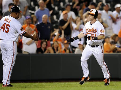 Baltimore Orioles' Lew Ford (51) rounds the bases as he is greeted by third base coach DeMarlo Hale (45) after hitting a home run during the third inning of a baseball game against the Chicago White Sox, Tuesday, Aug. 28, 2012, in Baltimore. (AP Photo/Nick Wass)