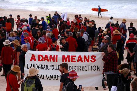 A surfer carries his board as he walks behind protesters participating in a national Day of Action against the Indian mining company Adani's planned coal mine project in north-east Australia, at Sydney's Bondi Beach in Australia, October 7, 2017.      REUTERS/David Gray