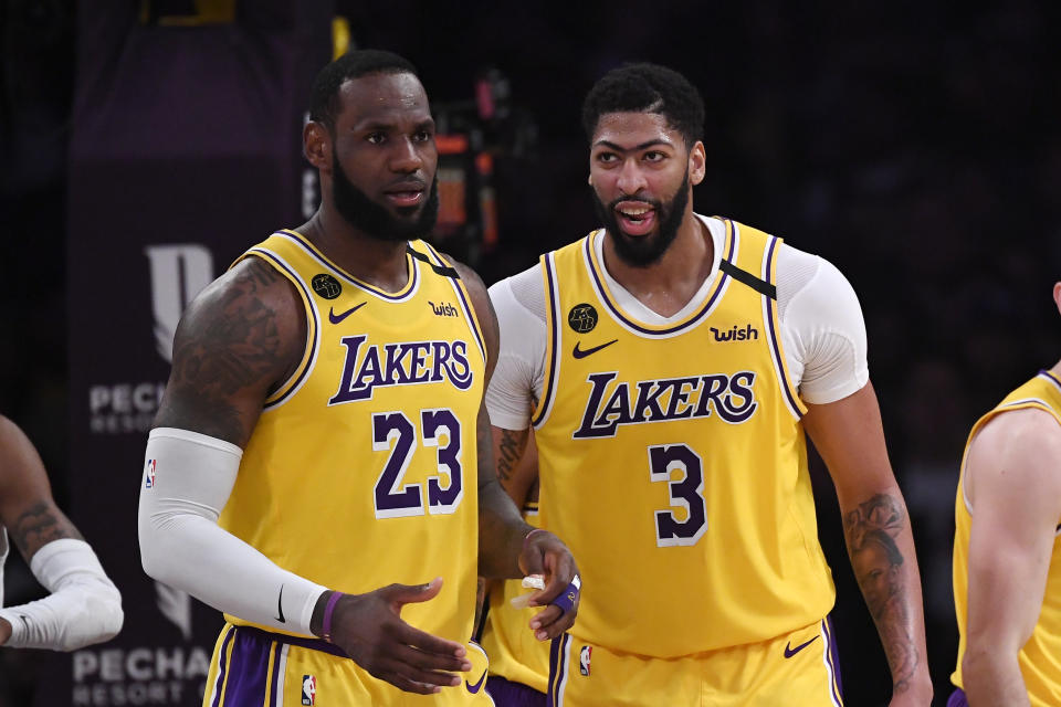 Los Angeles Lakers forward LeBron James, left, stands with forward Anthony Davis during the second half of an NBA basketball game against the Memphis Grizzlies Friday, Feb. 21, 2020, in Los Angeles. The Lakers won 117-105. (AP Photo/Mark J. Terrill)