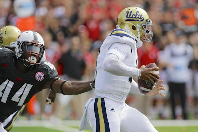 UCLA quarterback Brett Hundley (17) slips past Nebraska defensive end Randy Gregory (44) in the first half of an NCAA college football game in Lincoln, Neb., Saturday, Sept. 14, 2013. (AP Photo/Nati Harnik)
