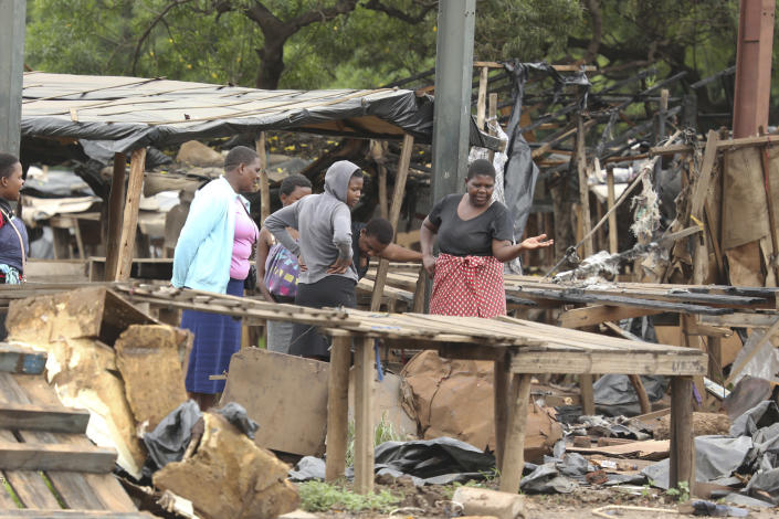 Women inspect their stalls at a market after they were destroyed during demonstrations over the hike in fuel prices in Harare, Zimbabwe, Tuesday, Jan. 15, 2019. Soldiers moved in to disperse crowds at the busy intersection and transport hub in Harare amid Zimbabwe's biggest unrest since deadly post-election violence in August. (AP Photo/Tsvangirayi Mukwazhi)