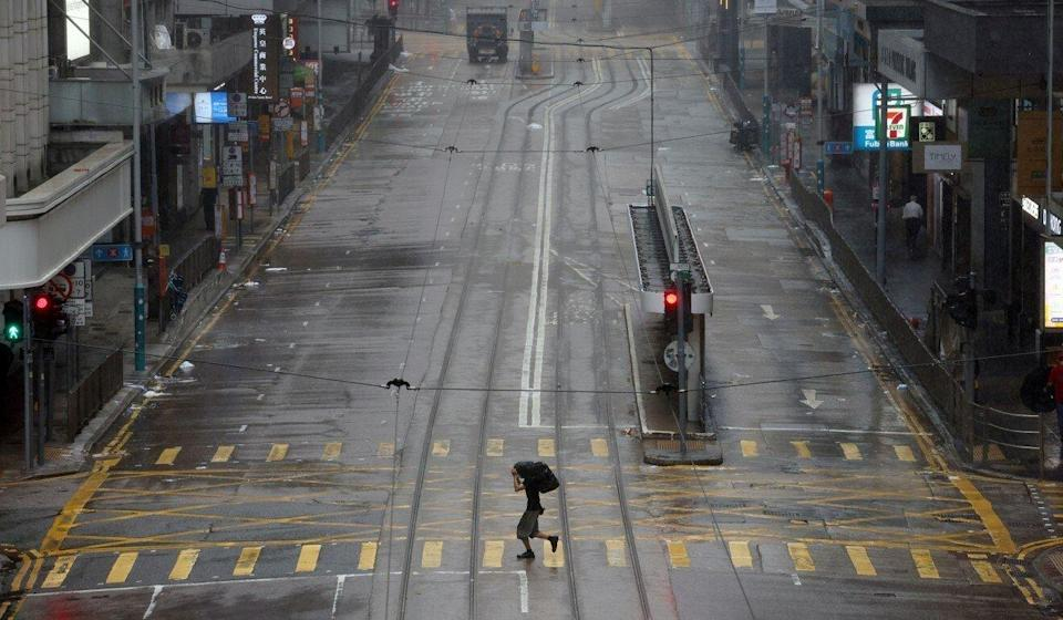 A man dashes across an empty street in Hong Kong's normally busy Central district during Wednesday No 8 typhoon warning. Photo: Nora Tam