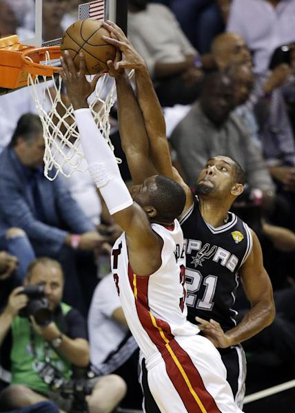 San Antonio Spurs forward Tim Duncan (21) blocks a shot by Miami Heat shooting guard Dwyane Wade (3) during the first half of Game 6 of the NBA Finals basketball game, Tuesday, June 18, 2013 in Miami. (AP Photo/Wilfredo Lee)