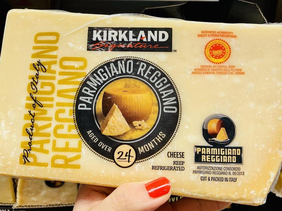 A hand holding a block of Kirkland parmigiano reggiano in the cheese section