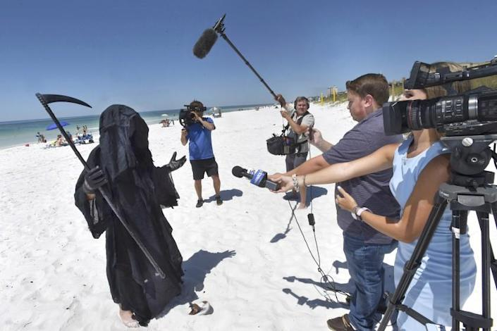 "Florida Attorney Daniel Uhlfelder, dressed as the Grim Reaper, talks with reporters after walking the newly-opened beach near Destin, Fla., Friday, May 1, 2020. Uhlfelder was protesting the Walton County, Fla., Commission's decision to reopen the county's beaches in spite of the COVID-19 pandemic. ""In these circumstances, I can see no rational reason to open our beaches, effectively inviting tens of thousands of tourists back into our community,"" Uhlfelder said in a news release. ""If by dressing up as the ""Grim Reaper"" and walking our beaches I can make people think and potentially help save a life – that is the right thing to do."" (Devon Ravine/Northwest Florida Daily News via AP)"