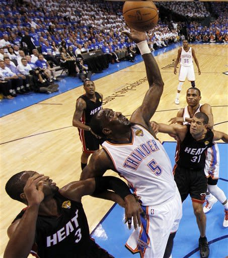 Oklahoma City Thunder center Kendrick Perkins (5) goes after a rebound against Miami Heat power forward Chris Bosh and small forward Shane Battier during the first half at Game 2 of the NBA finals basketball series, Thursday, June 14, 2012, in Oklahoma City. (AP Photo/Jim Young, Pool)