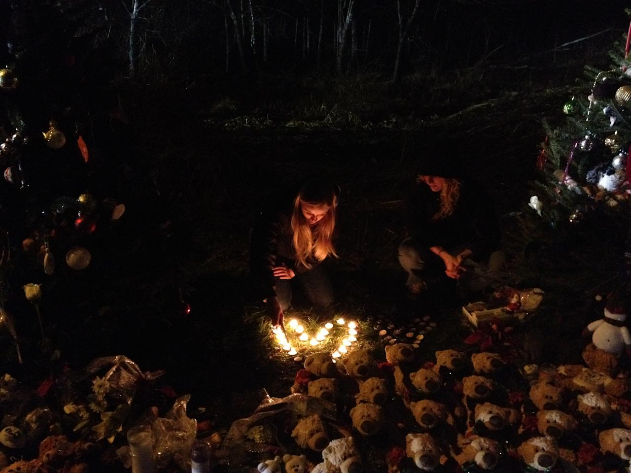 <p>A girl lights candles displayed in shape of heart near the entrance to Sandy Hook Elementary School in Newtown, Conn., Dec. 15, 2012. (Dylan Stableford/Yahoo News) </p>