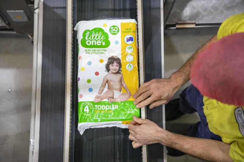 Woolworths Little One's nappies are pictured on a conveyor belt.