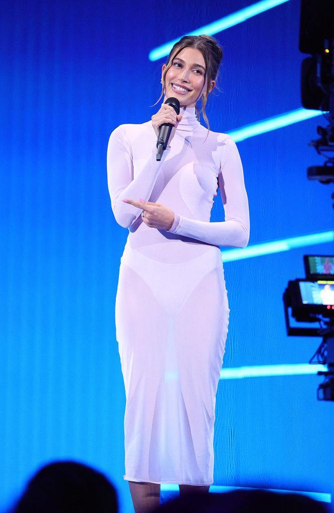 Hailey Bieber speaks wore a sheer lilac dress to present an award at the 2021 MTV Video Music Awards. (Getty Images)