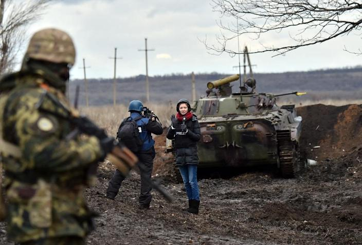 A TV journalist prepares to do a piece to camera in front of an armoured personnel carrier on the frontline between Ukrainian forces and pro-Russian separatists, near Debaltseve, in the Donetsk region (AFP Photo/Sergei Supinsky)