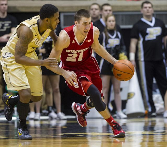 Wisconsin's Josh Gasser (21) races past Purdue's Terone Johnson (0) as he brings the ball up court in the second half of an NCAA college basketball game, Saturday, Jan. 25, 2014, in West Lafayette, Ind. Wisconsin defeated Purdue 72-58. (AP Photo/Doug McSchooler)