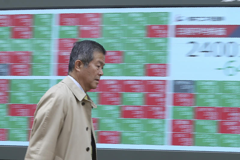 In this Wednesday, Dec. 18, 2019, photo, a man walks by an electronic stock board of a securities firm in Tokyo. Stocks were mixed in early trading in Asia on Friday, Dec. 20, 2019, after Wall Street posted more record highs, extending the market's gains for the week. (AP Photo/Koji Sasahara)