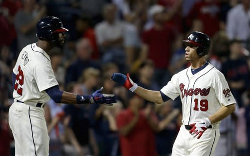 Atlanta Braves' Andrelton Simmons, right, high-fives teammate Jason Heyward after scoring off a double by Martin Prado in the fifth inning of a baseball game against the New York Mets Saturday, Sept. 29, 2012, in Atlanta. (AP Photo/David Goldman)