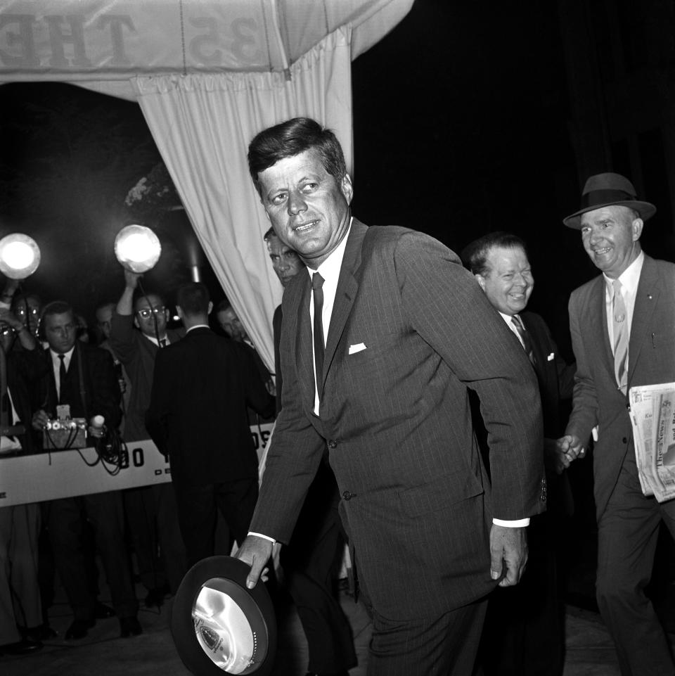 President Kennedy, hat in hand, leans slightly forward as he glances at bystanders upon his arrival at the Carlyle Hotel here September 19th.  The Chief Executive is scheduled to address the 18th session of the United Nations General Assembly September 20th.  He is expected to discuss the partial nuclear test ban treaty and prospects for further reductions in East-West tensions.