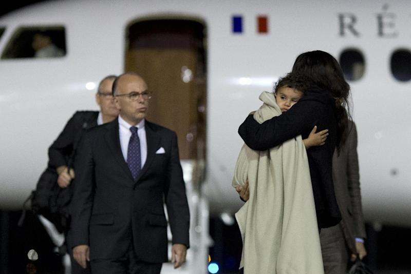 French Interior Minister Bernard Cazeneuve (L) welcomes Meriam Rhaiem (R) upon her arrival with her daughter on September 3, 2014 in Vélizy-Villacoublay near Paris (AFP Photo/Kenzo Tribouillard)