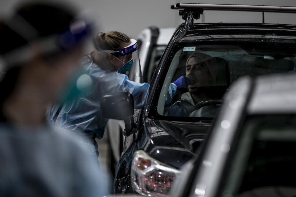 A health worker takes a throat swab sample of a man for a Covid-19 test at the drive through Covid-19 testing point Montague in Melbourne. Source: AAP