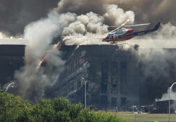 A rescue helicopter surveys damage to the Pentagon as firefighters battle flames after an airplane crashed into the U.S. military Headquarters outside of Washington in an apparent terrorist attack, September 11, 2001. <br><br>(REUTERS/Larry Downing LSD/HB)