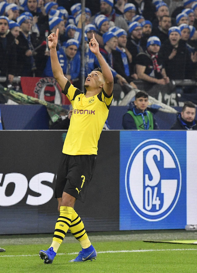 Dortmund's Jadon Sancho celebrates in front of Schalke fans after scoring his side's second goal against Schalke goalkeeper Ralf Faehrmann during the German Bundesliga soccer match between FC Schalke 04 and Borussia Dortmund at the Arena in Gelsenkirchen, Germany, Saturday, Dec. 8, 2018. (AP Photo/Martin Meissner)