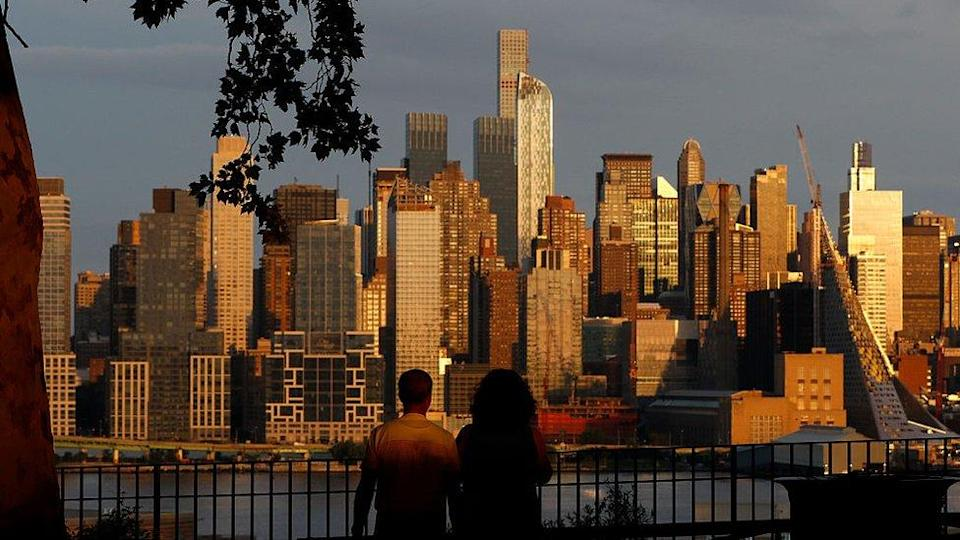 People in West New York, New Jersey watch the sun set on New York, August 23, 2015.