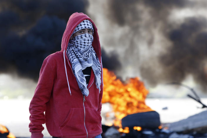 Palestinian protestor stands during clashes with Israeli troops at the Hawara checkpoint, south of the West Bank city of Nablus, Friday, Dec. 14, 2018. (AP Photo/Majdi Mohammed)